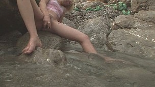 Freaky Alice rubbing against a rock to get her pussy moist